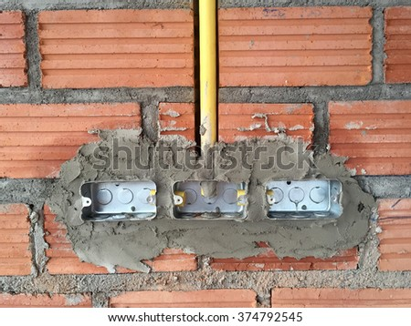 electric sockets installation in brick walls at house construction site - stock photo