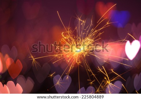 Electric sparklers with heart bokeh background - stock photo
