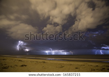 Electric storm in the beach, sand clouds and thunders. - stock photo