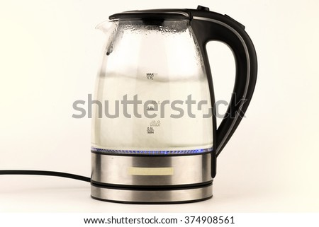 electric teapot kettle with a boiling water inside and color backlight isolated in white background - stock photo