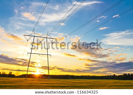 Electric towers on a field with sunset - stock photo