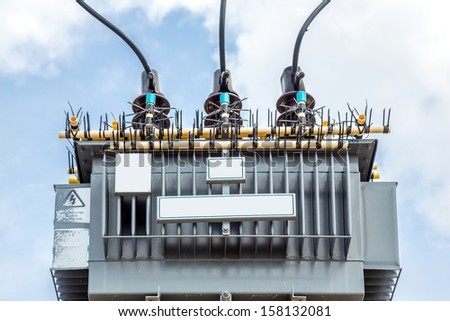 Electric transformer against Blue Sky - stock photo