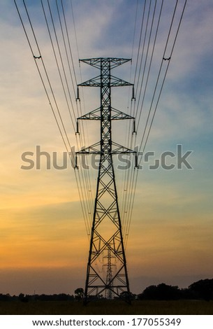 Electric transmission tower with sunset light blackground. - stock photo
