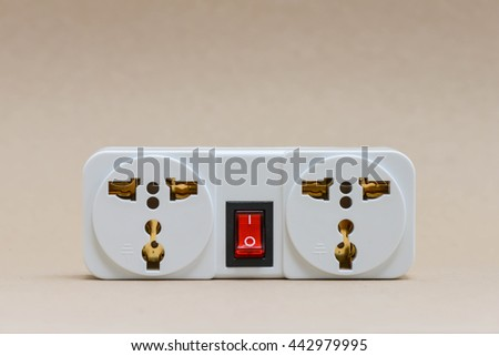Electric travel outlet with red button switch on the brown background