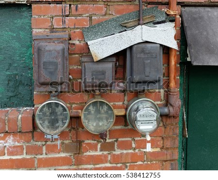 Electric utility meters attached to brick wall of rundown building. Horizontal.