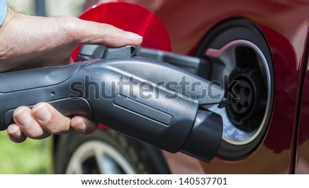 electric vehicle plugging in - stock photo