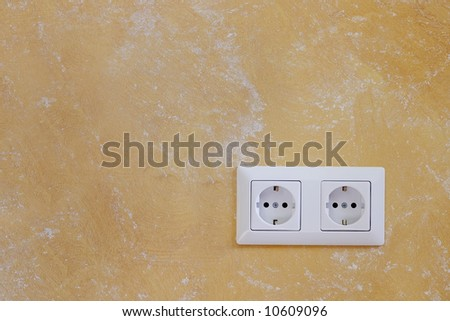 Electric wall plug at a orange wall - stock photo