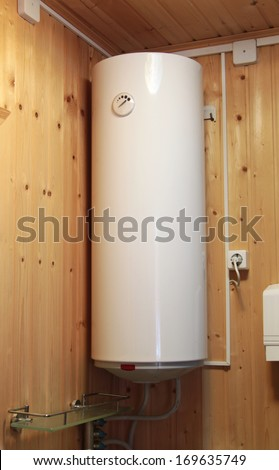 electric water heater hanging on the wooden wall - stock photo