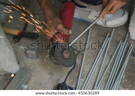 Electric wheel grinding on steel structure by worker in factory - stock photo