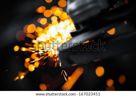 Electric wheel grinding on steel structure in factory - stock photo