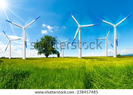 Electric Wind Generators in Countryside. Six wind turbines in countryside with tree, blue sky, clouds and sun rays - stock photo