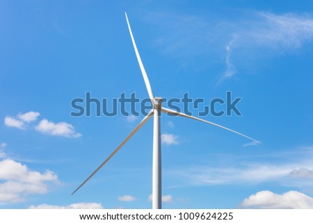 Electric wind turbine with blue sky and clouds.