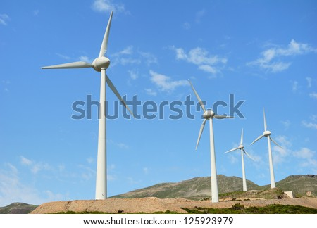Electric Windmills on a hill and blue sky - stock photo