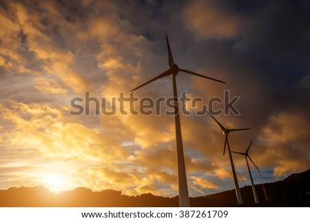 Electric windmills on the sky background on the sunset