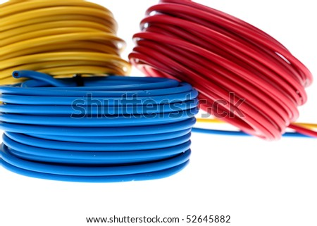 Electric wires of red, yellow and dark blue colour are winded in rings.