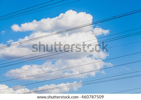 Electric wires strung against blue sky and beautiful clouds