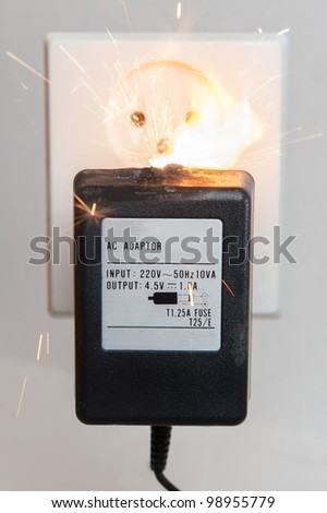 Electrical adapter with failure causing a fire - stock photo