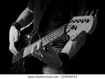 electrical bass guitar in hands, black and white - stock photo