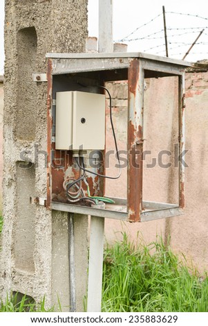 Electrical box placed in an old metal frame on a pole - stock photo