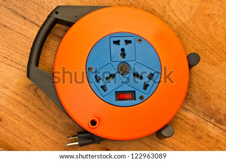 Electrical cable extension reel isolated on wood background - stock photo