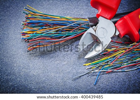 Electrical cables sharp wire cutter on black background electricity concept. - stock photo
