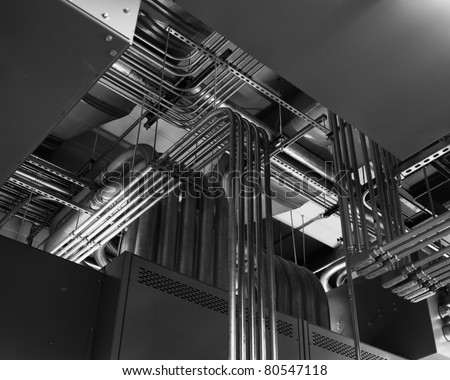 Electrical conduits run along a ceiling in a switchgear room. - stock photo
