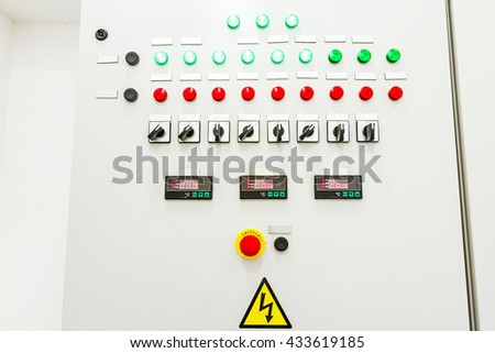 Electrical control panel containing has a digital temperature gauge with warning sticker and an emergency shutdown (panic) button. - stock photo