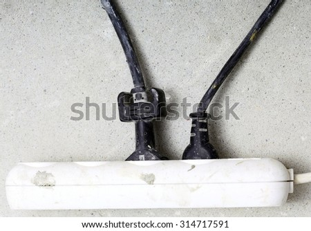 electrical cords connected to a power strip or extension block in construction site - stock photo