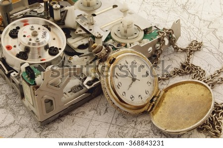 Electrical device and mechanical pocket watch. Abstract concept: ancient and modern technology.  - stock photo