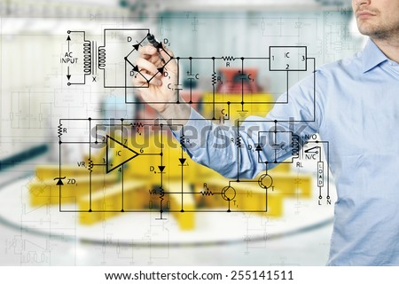 electrical engineer draws a diagram of a circuit. power plant interior in background - stock photo