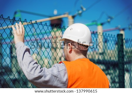 Electrical engineer touched a hand to the fence