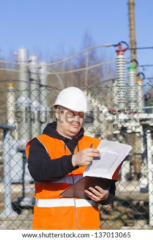 Electrical engineer with documentation near to the electric substations - stock photo