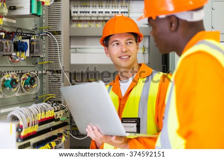 electrical engineers adjusting transformer settings in control room - stock photo