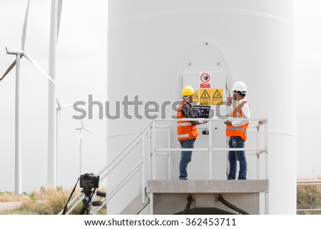Electrical engineers and technician working in wind turbine power generator station with laptop computer - stock photo