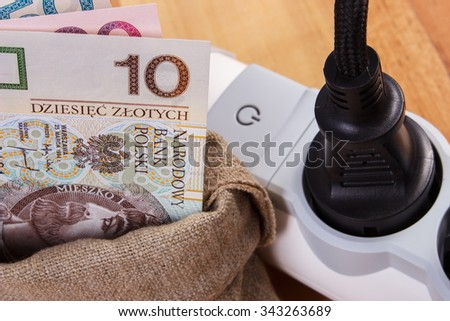Electrical extension with connected plug and polish currency money in jute bag, concept of saving money on electricity, energy costs - stock photo