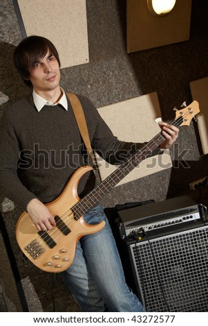 electrical guitar player near amplifier. focus on pouch of jeans - stock photo