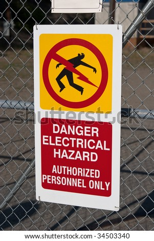 Electrical hazard sign, authorized personnel only on chain-link fence - stock photo