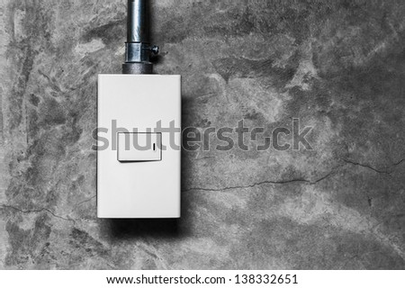 electrical light switch with pipeline on concrete background - stock photo