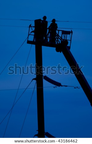 Electrical linemen morking out of a bucket on power lines - stock photo