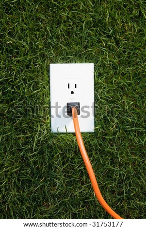 Electrical outlet in grass with extension cord plugged in - stock photo