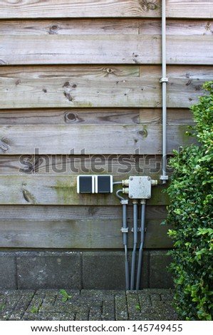 Electrical outlet on the garden wall - stock photo