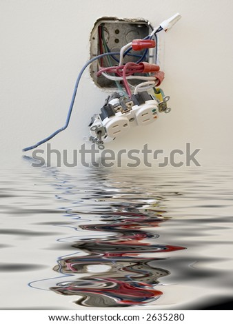 Electrical outlet reflected in floodwater in office - stock photo