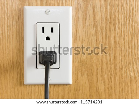 Electrical outlet with black power cord. Home interior electrical outlet with black power cord and plug against wood textured paneling. - stock photo