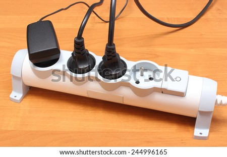 Electrical plugs with cords connected to electrical power strip, electrical extension for appliances with On-Off switch, concept of energy saving - stock photo