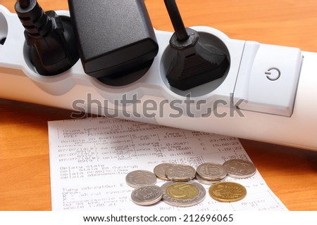 Electrical plugs with cords connected to electrical power strip with On-Off switch, electricity bill with heap of coins, concept of energy saving - stock photo