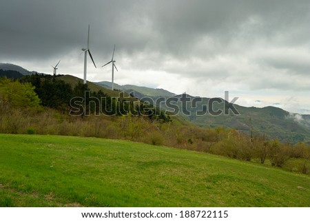 Electrical power generating wind turbines on the Maritime Alps (Italy) with storm cloud in the sky. - stock photo