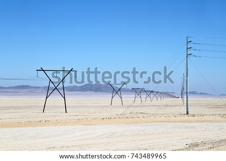 Electrical power lines on pylons stretch into the distance in a dry, desert landscape.