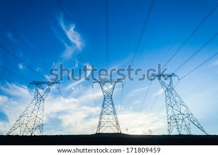 Electrical Power Lines Towers Electrical power line cables suspended from steel towers transporting energy supply to consumers in homes and economy. - stock photo