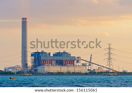 electrical power plant near the sea coat with the sunset light. - stock photo