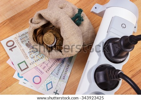 Electrical power strip with connected plug and polish currency money on wooden floor, power board, concept of saving money on electricity, energy costs - stock photo
